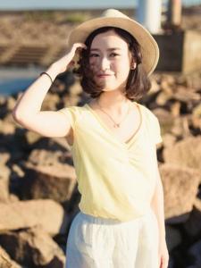 海岸礁石上的亮麗草帽美女秀發飄揚