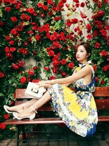 玫瑰花圃里的清新靓丽美模坐在长椅上显青春活力