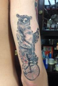 熊纹身 男生手臂上骑自行车的狗熊纹身图片