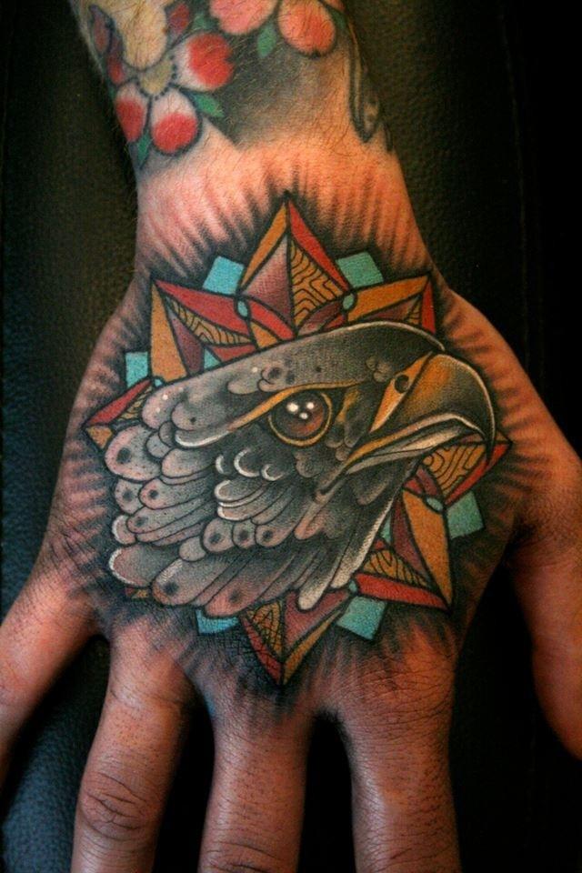 手背黑色old school老鷹頭像與星星紋身圖案