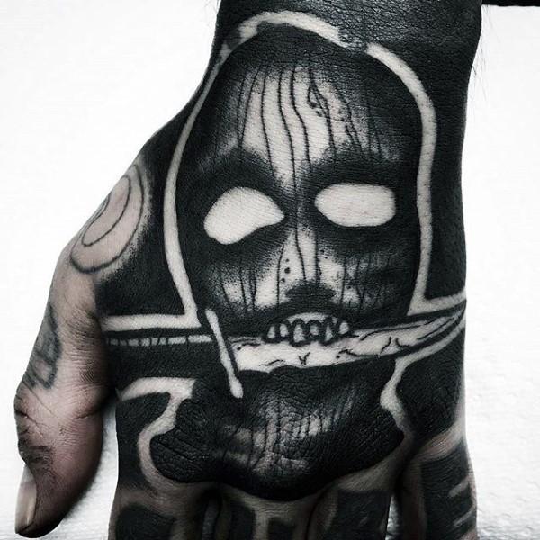 手背黑色疯狂的面具与匕首纹身图案