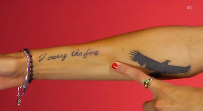 手臂黑色的字母和大鸟纹身图案
